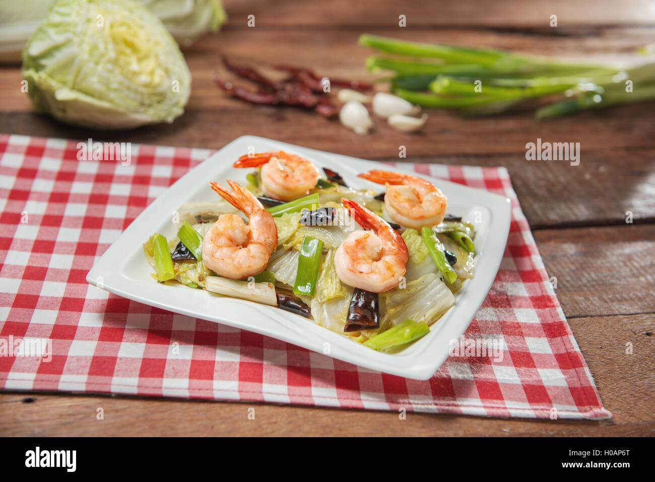 Plate of fried shrimp with vegetables on the table in restaurant - Stock Image