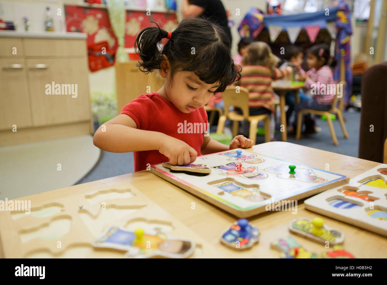 A girl playing with a jigsaw at the Sure Start Palfrey Nursery in Walsall, West Midlands. - Stock Image