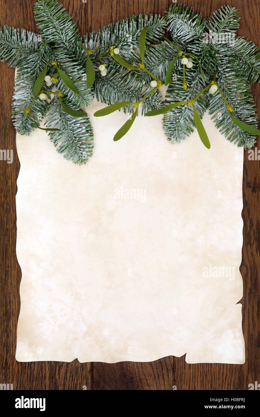 Christmas abstract background border with mistletoe and snow covered fir on parchment paper over old oak background. - Stock Image