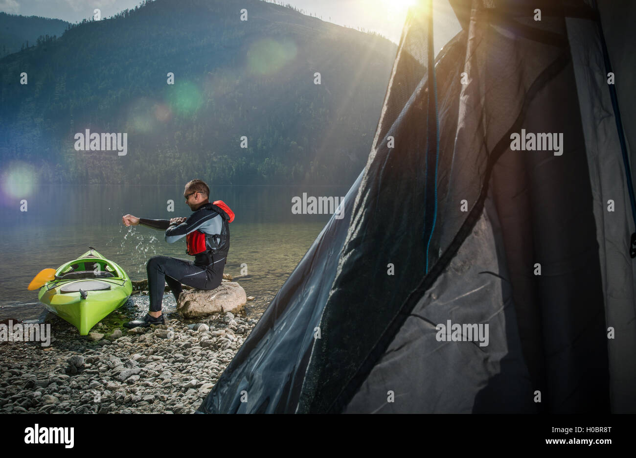 Camping on the Lake Shore. Men Relaxing on the Edge of the Lake Side to His Kayak. - Stock Image