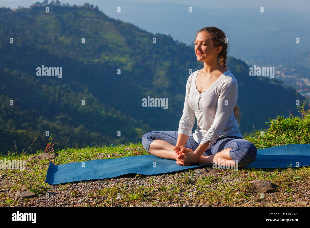 Sporty fit woman practices yoga asana Baddha Konasana outdoors - Stock Image