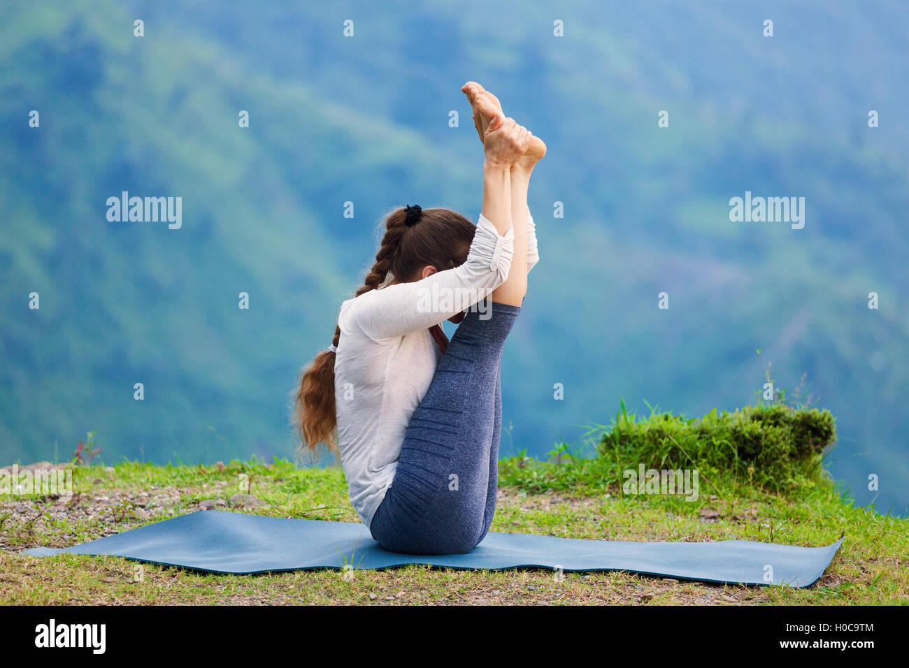 Woman practices yoga asana Urdhva mukha paschimottanasana - Stock Image