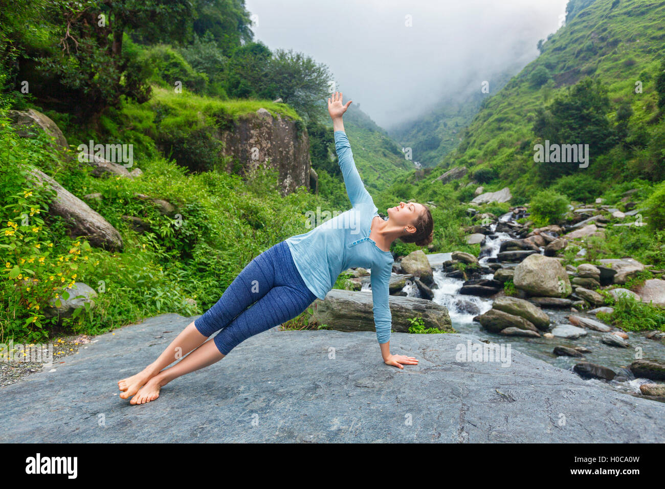 Woman doing yoga asana Vasisthasana - side plank pose outdoors - Stock Image