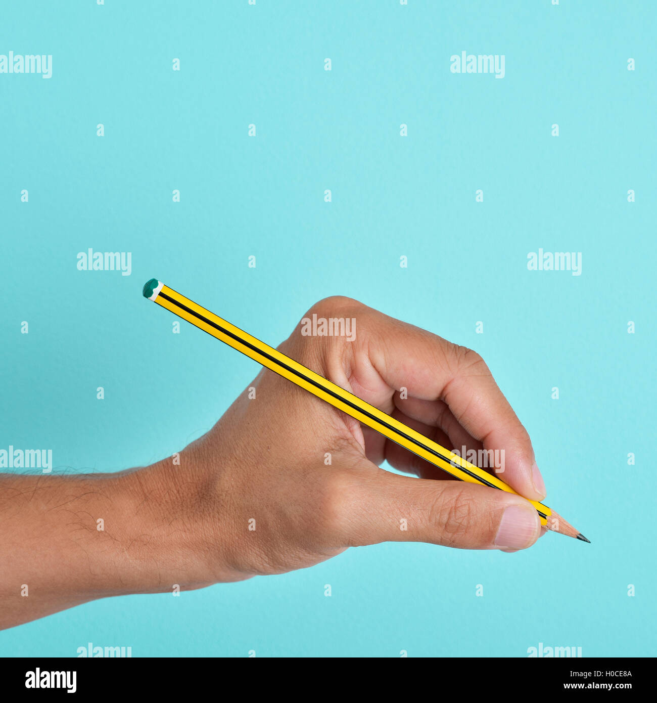 the hand of a left-handed man with a pencil, against a blue background - Stock Image