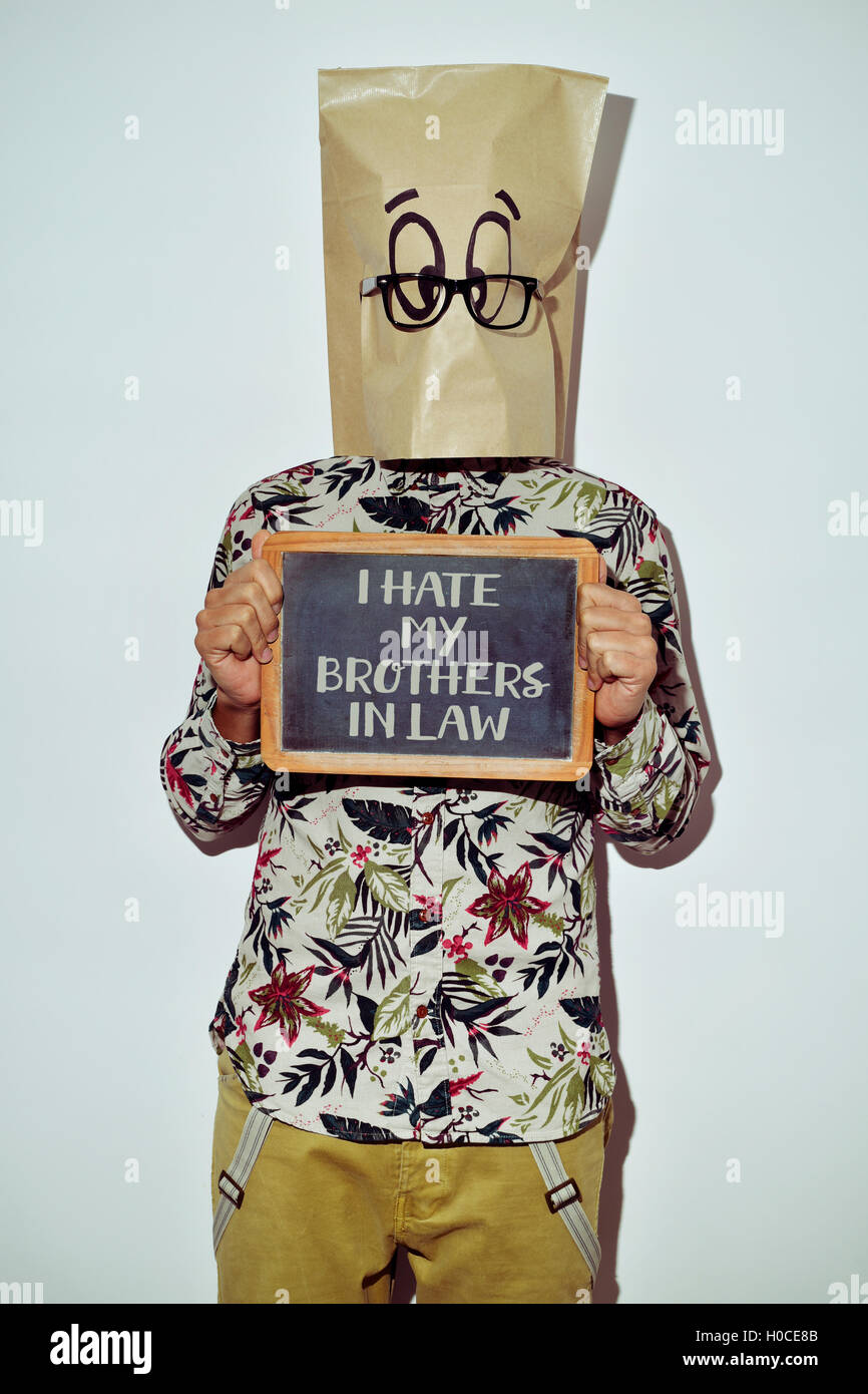 a young man dressing casual wear with a paper bag in his head shows a chalkboard with the text I hate my brothers - Stock Image