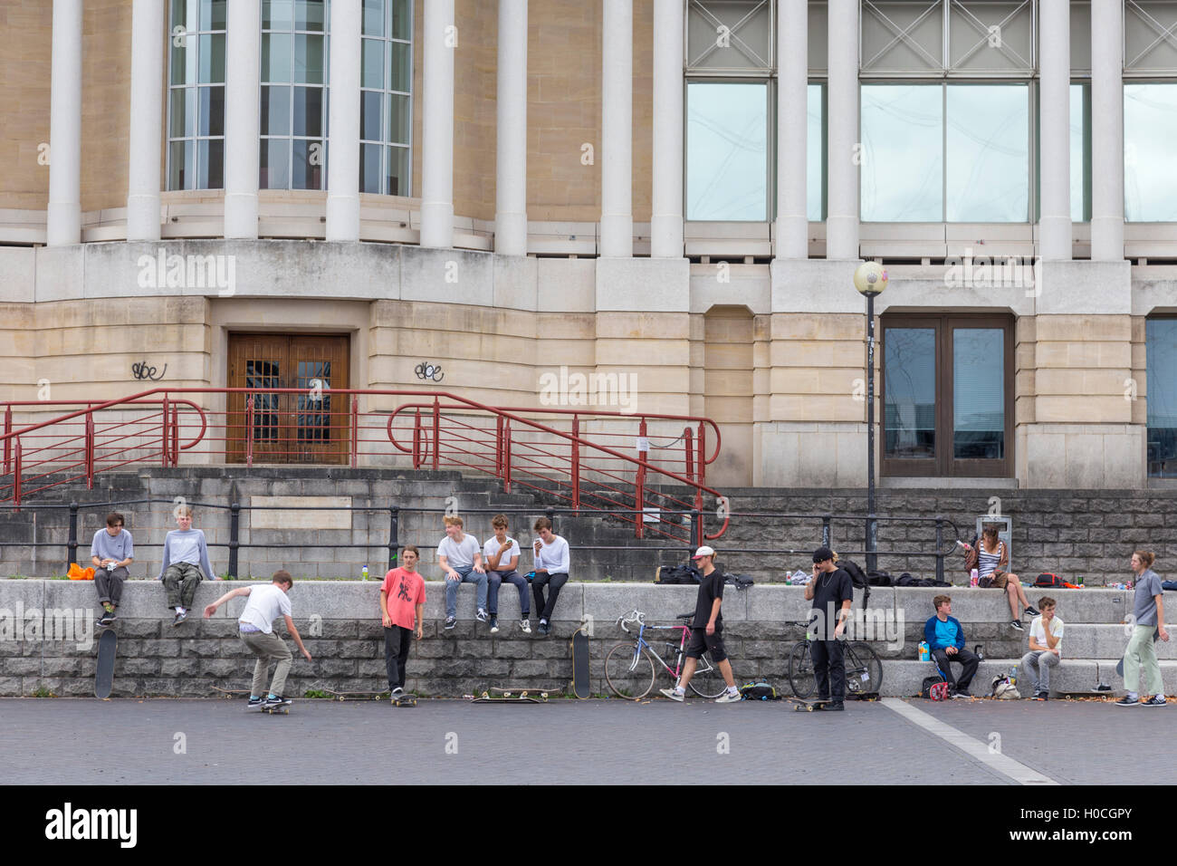 Youths skateboarding in Bristol City Harbour, Bristol, England, UK - Stock Image