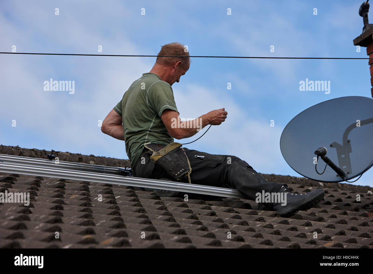 Workman Installing Rails And Wiring For Rooftop Solar Panel Array In Series A Domestic Installation The Uk
