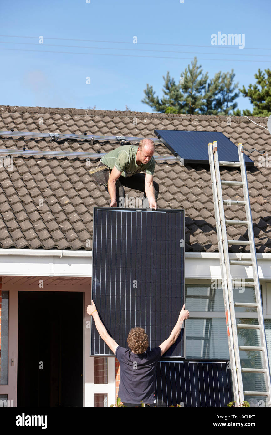 man installing rooftop solar panel array in a domestic solar panel installation in the uk - Stock Image