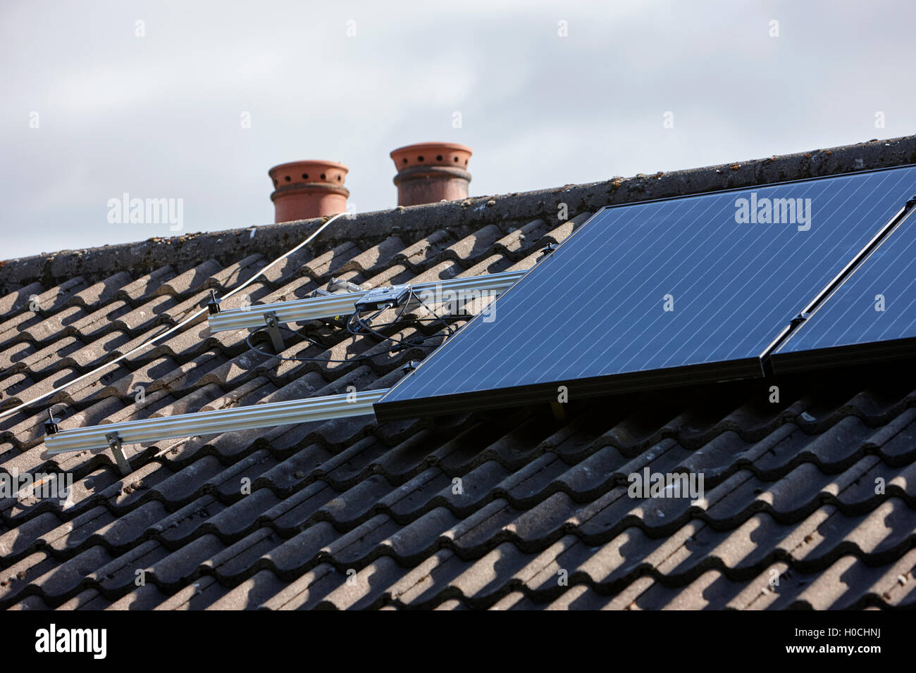 panels mounting rails and micro inverters in a domestic solar panel installation in the uk - Stock Image