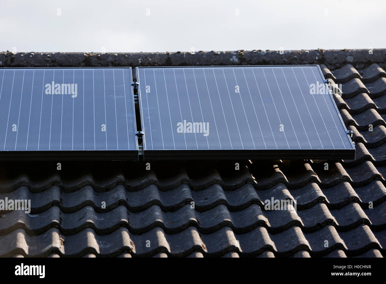 black premium roof mounted solar panels in a domestic solar panel installation in the uk - Stock Image