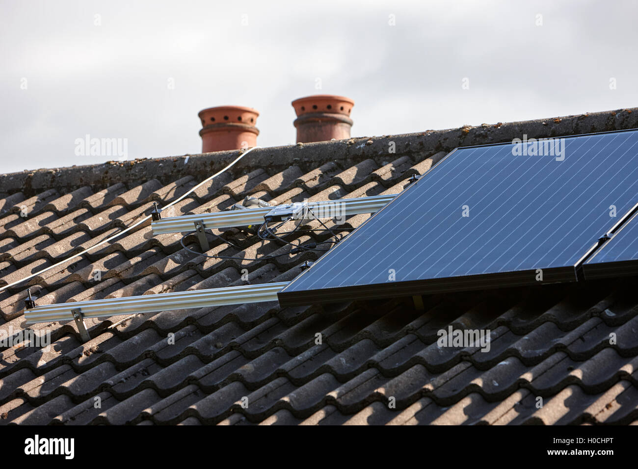 mounting system and micro inverters in a domestic solar panel installation in the uk - Stock Image