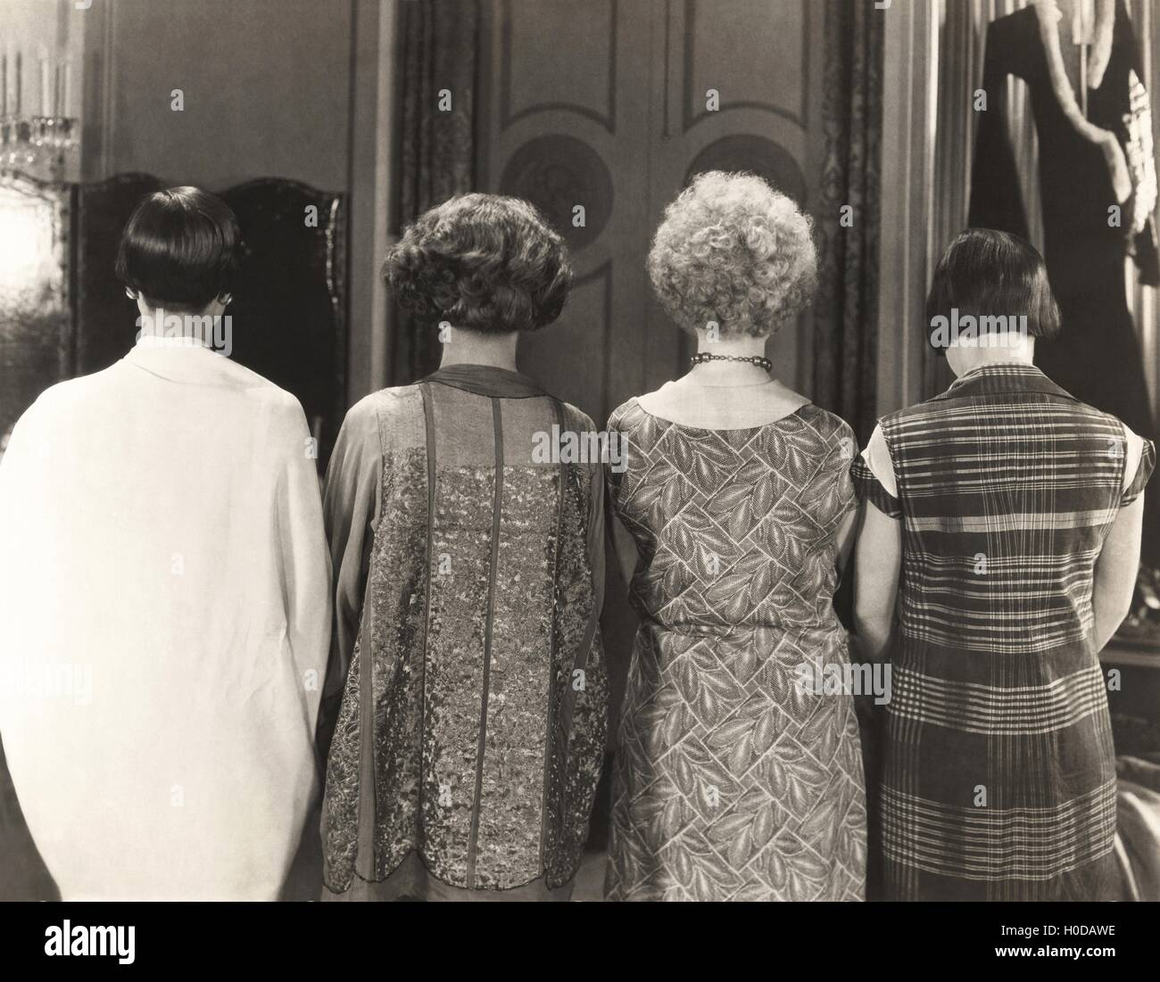 Rear view of four women standing in a row - Stock Image