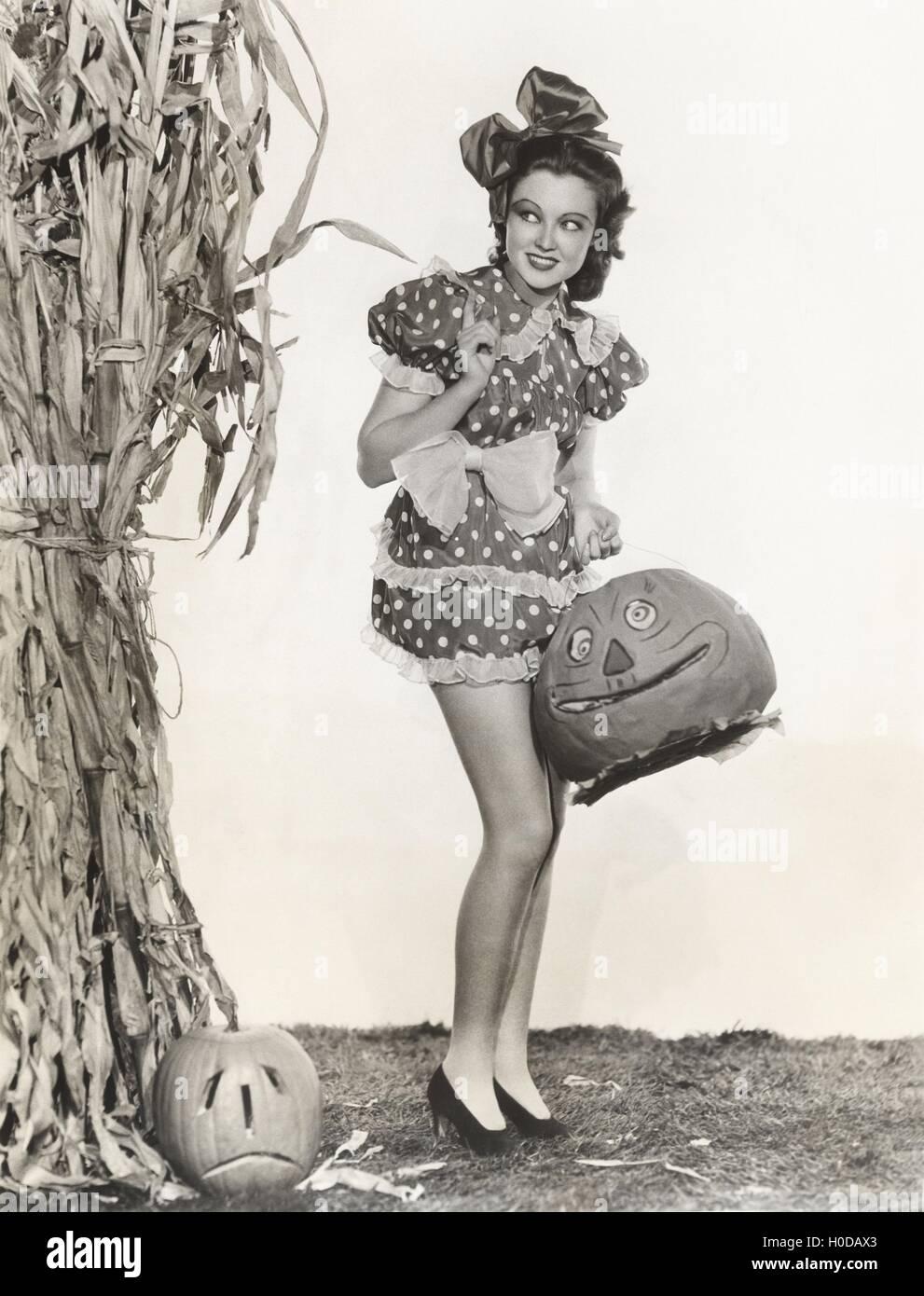 Woman in short polka dot dress in front of cornstalk carrying pumpkin - Stock Image