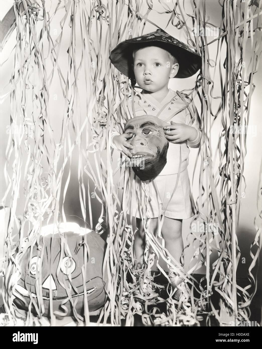 Little boy in Halloween costume holding mask standing by streamers - Stock Image