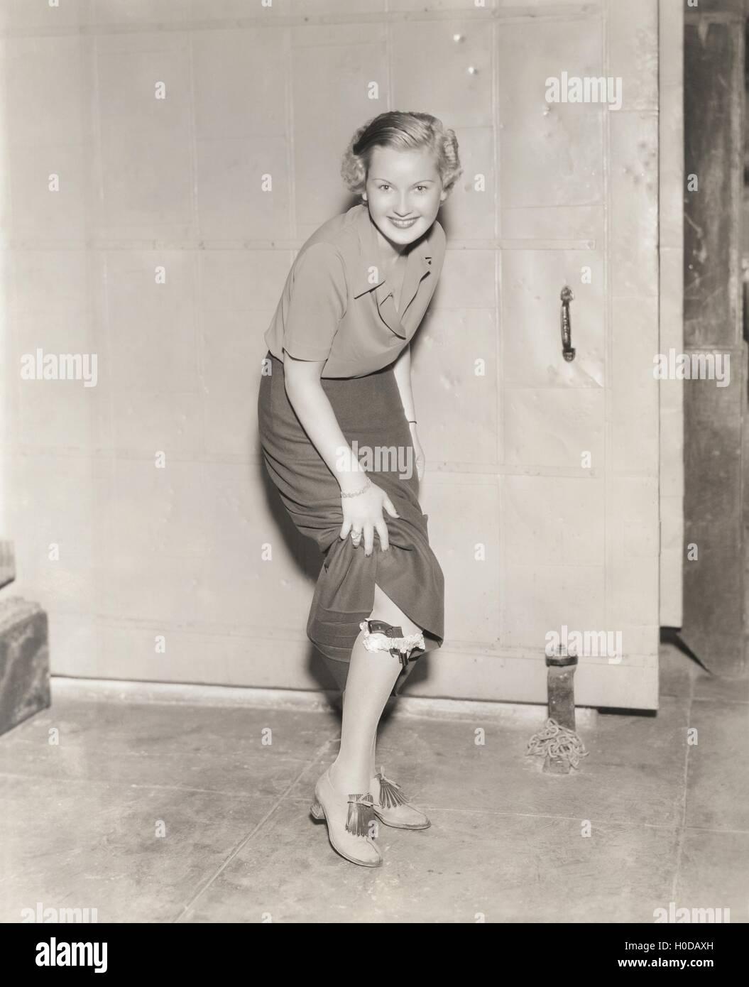 Woman hiding handgun in her garter - Stock Image