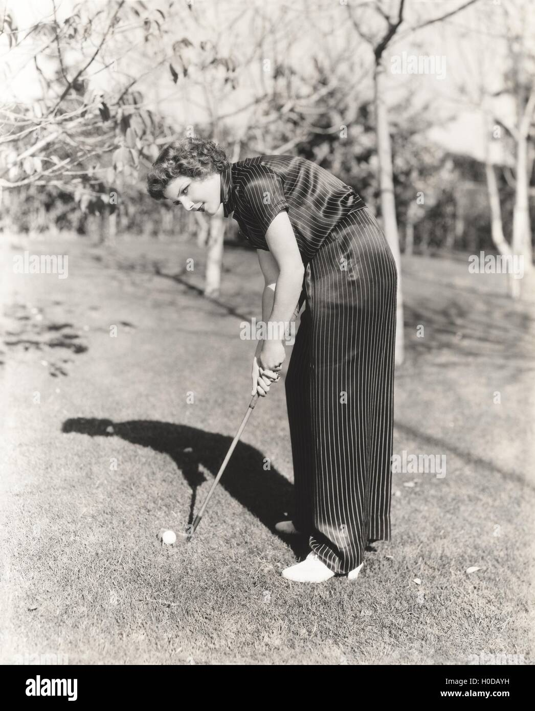 Full length portrait of young woman playing golf on field - Stock Image