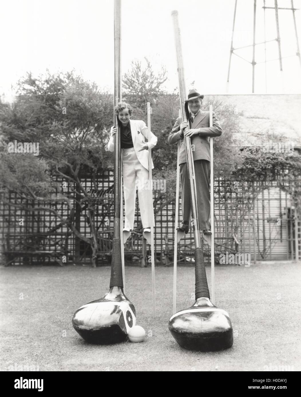 Man and woman on stilts holding giant golf clubs - Stock Image