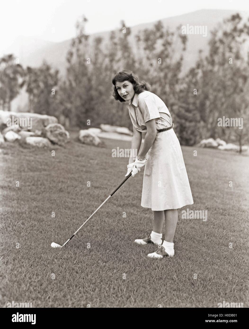 Woman in white gloves playing golf - Stock Image