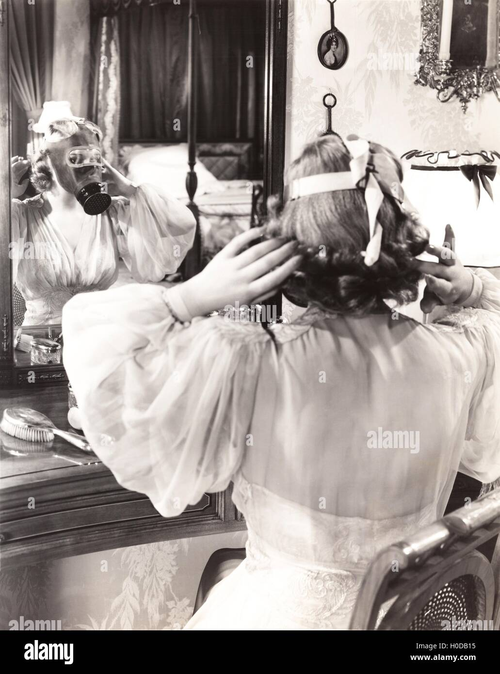 Woman in gas mask looking in mirror - Stock Image