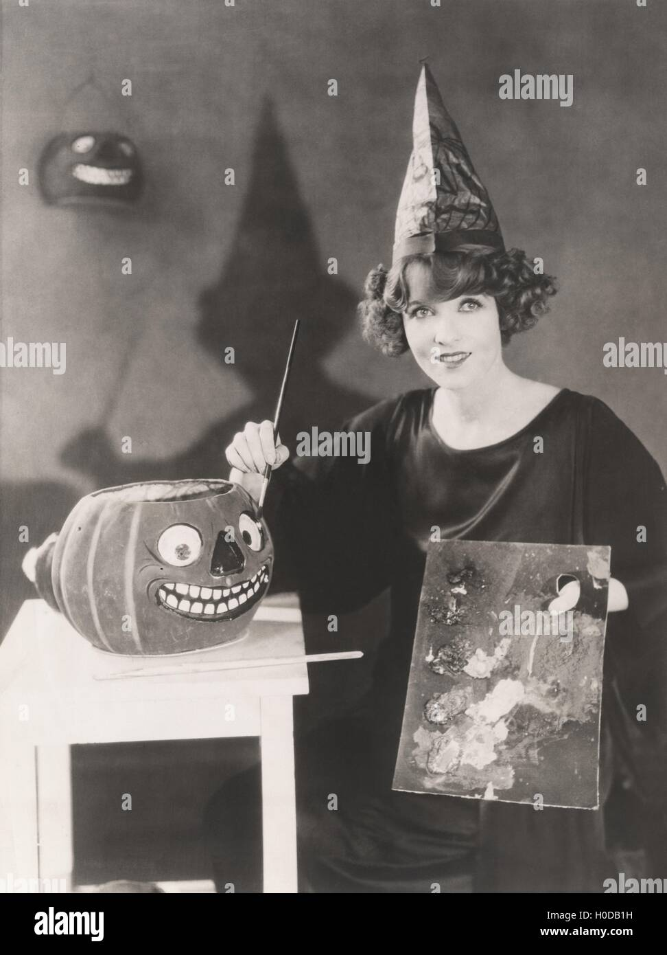 Woman in pointy hat painting a jack o'lantern - Stock Image