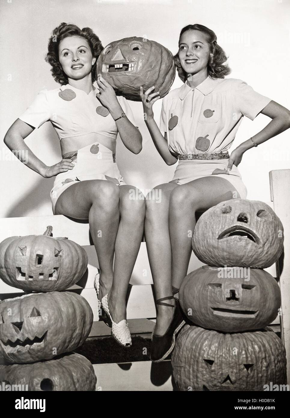 Two women sitting on fence with carved pumpkins - Stock Image