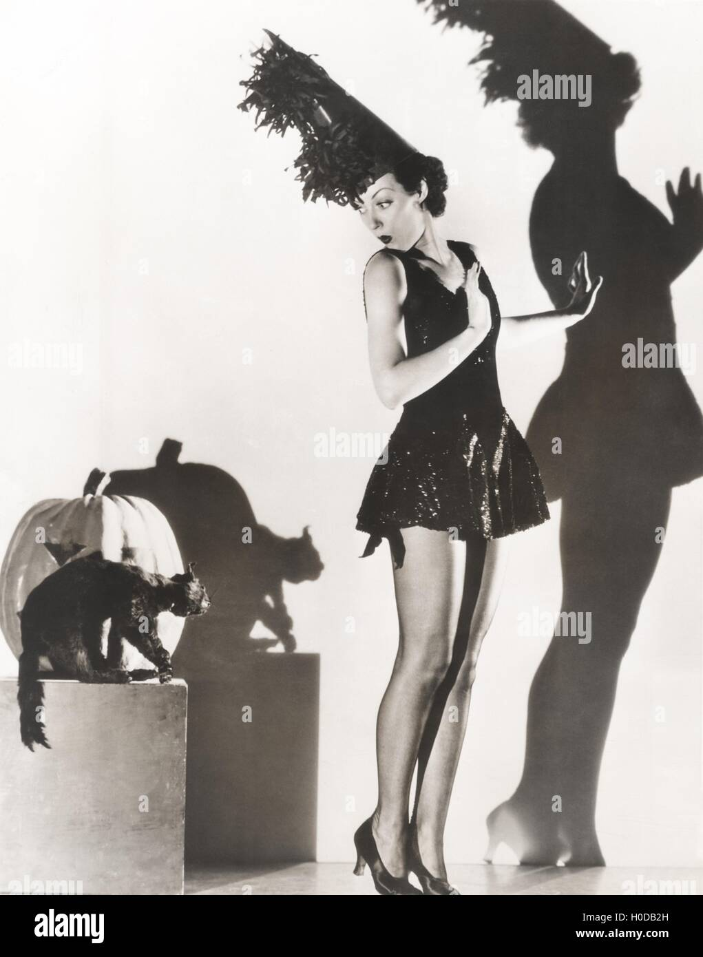 Black cat giving woman in costume the heebie-jeebies - Stock Image