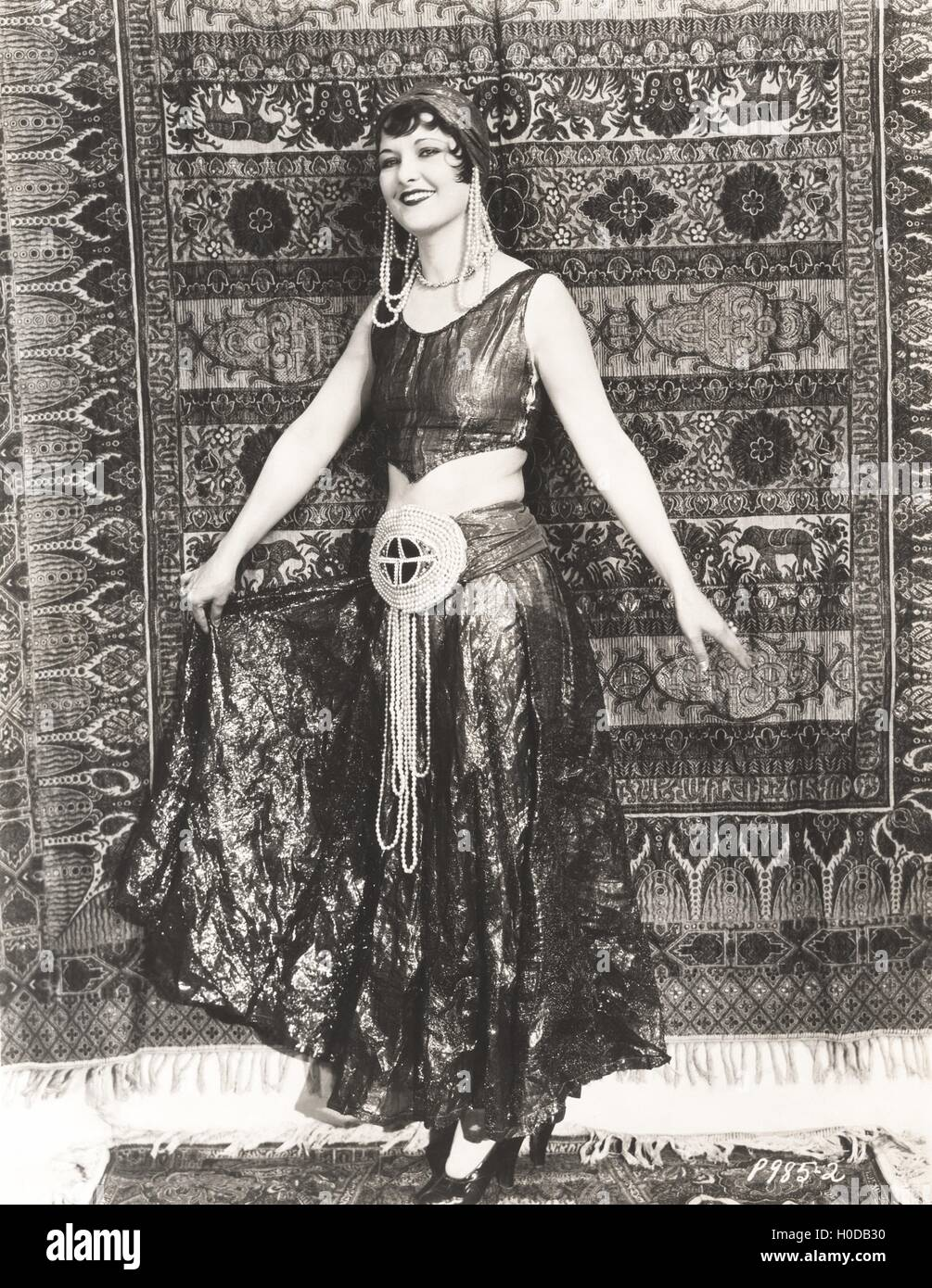 Woman dressed in gypsy costume standing in front of rug - Stock Image