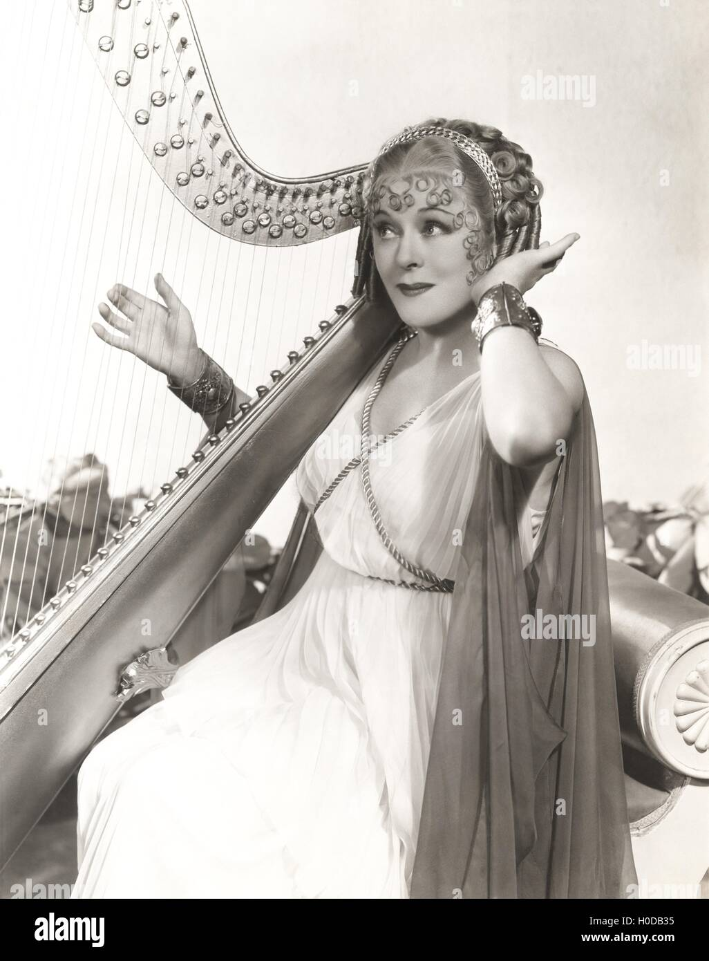 Woman in ancient Greek costume playing harp Stock Photo