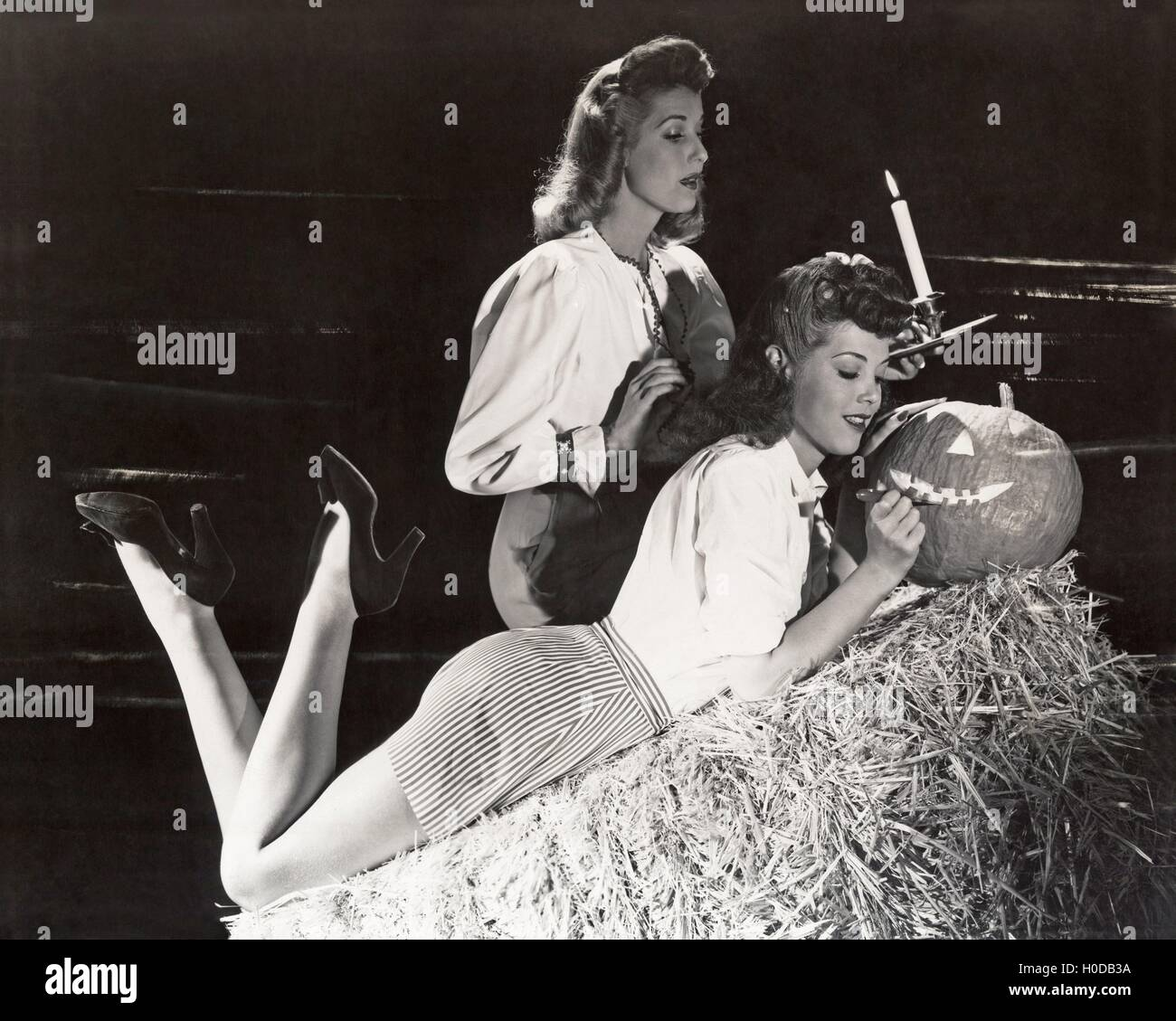 Two women in a barn carving jack o'lantern - Stock Image
