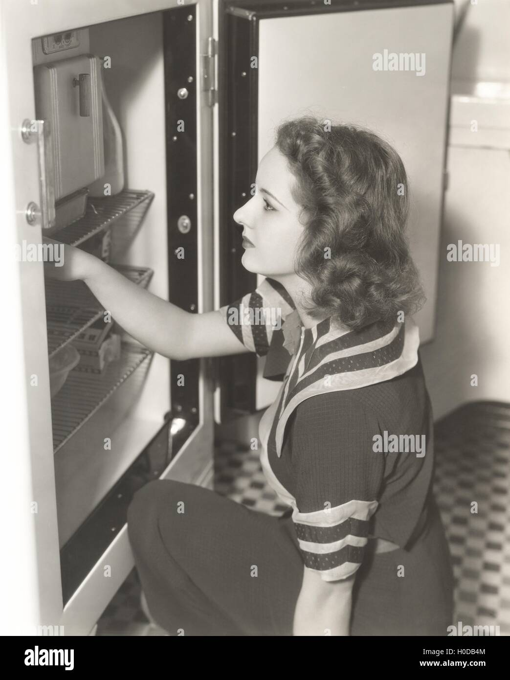 Side view of woman looking through refrigerator - Stock Image