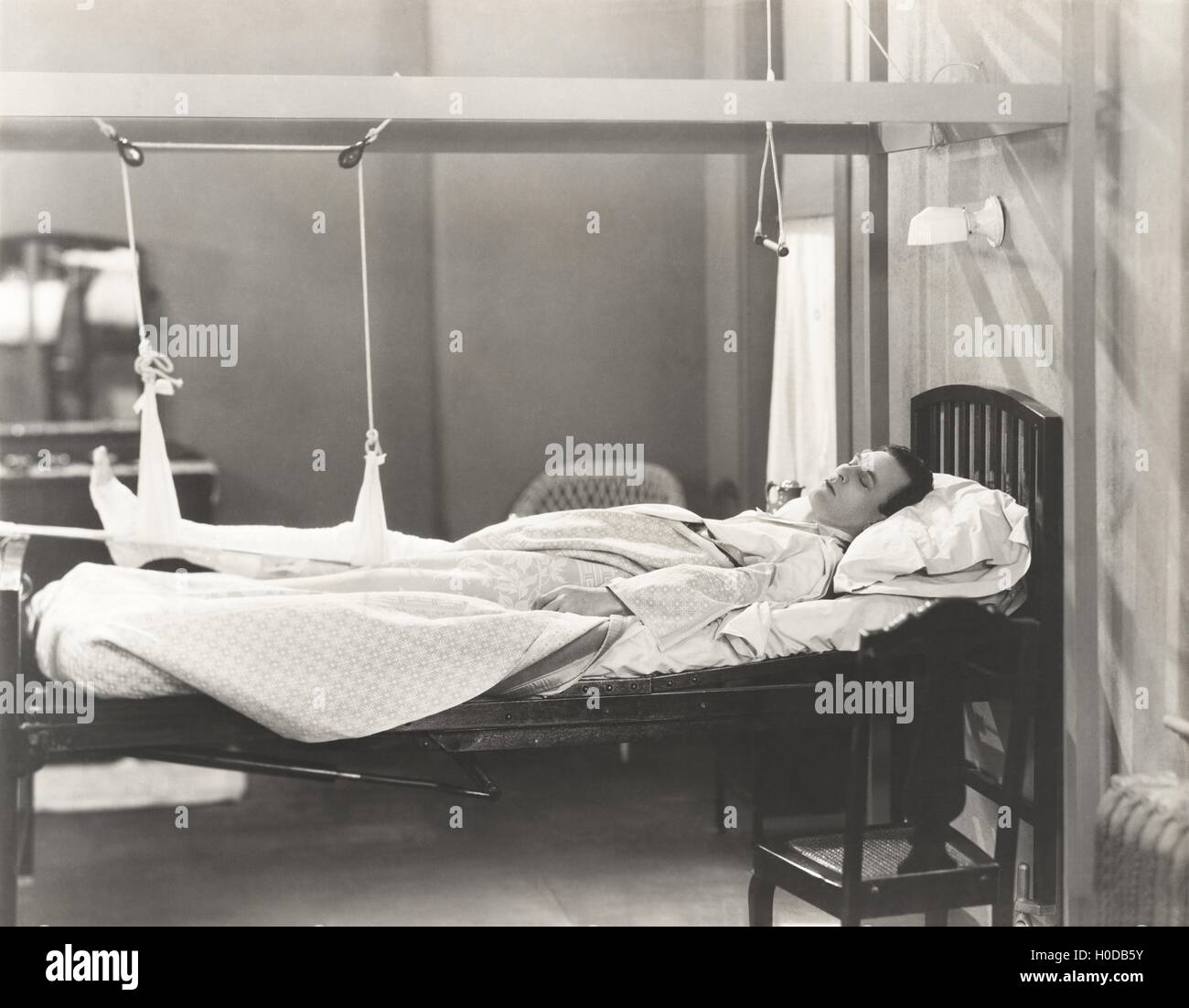 Man with fractured leg sleeping on hospital bed - Stock Image
