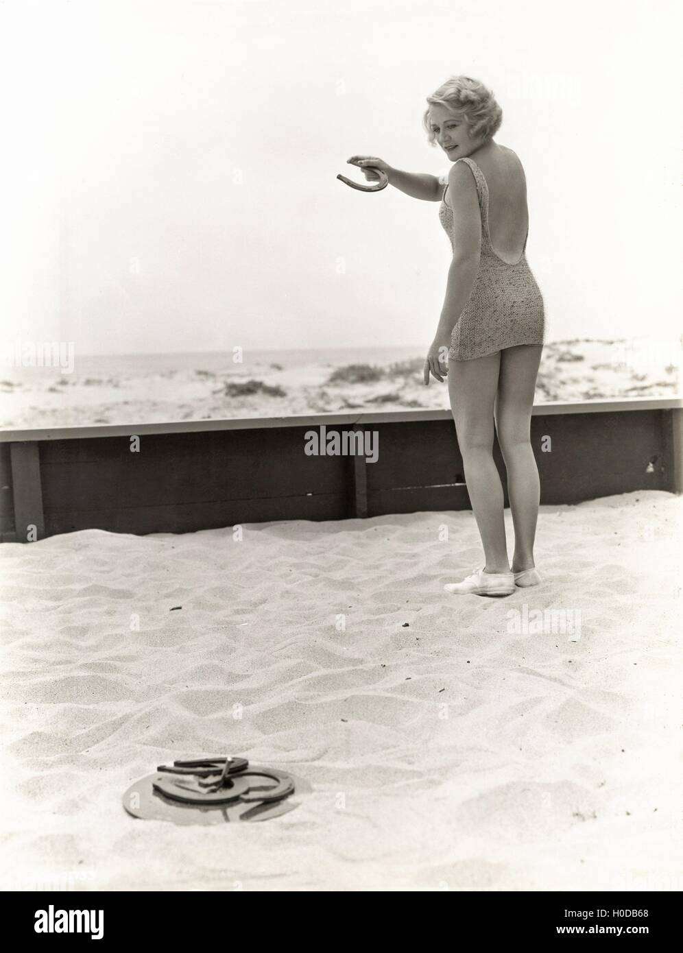 Rear view of woman playing horseshoes at the beach - Stock Image