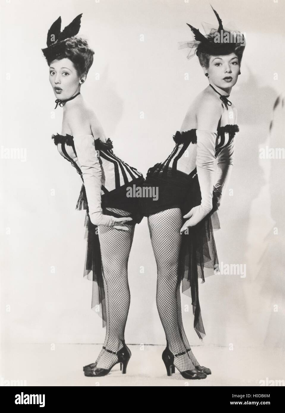 Women in matching costumes standing back to back - Stock Image