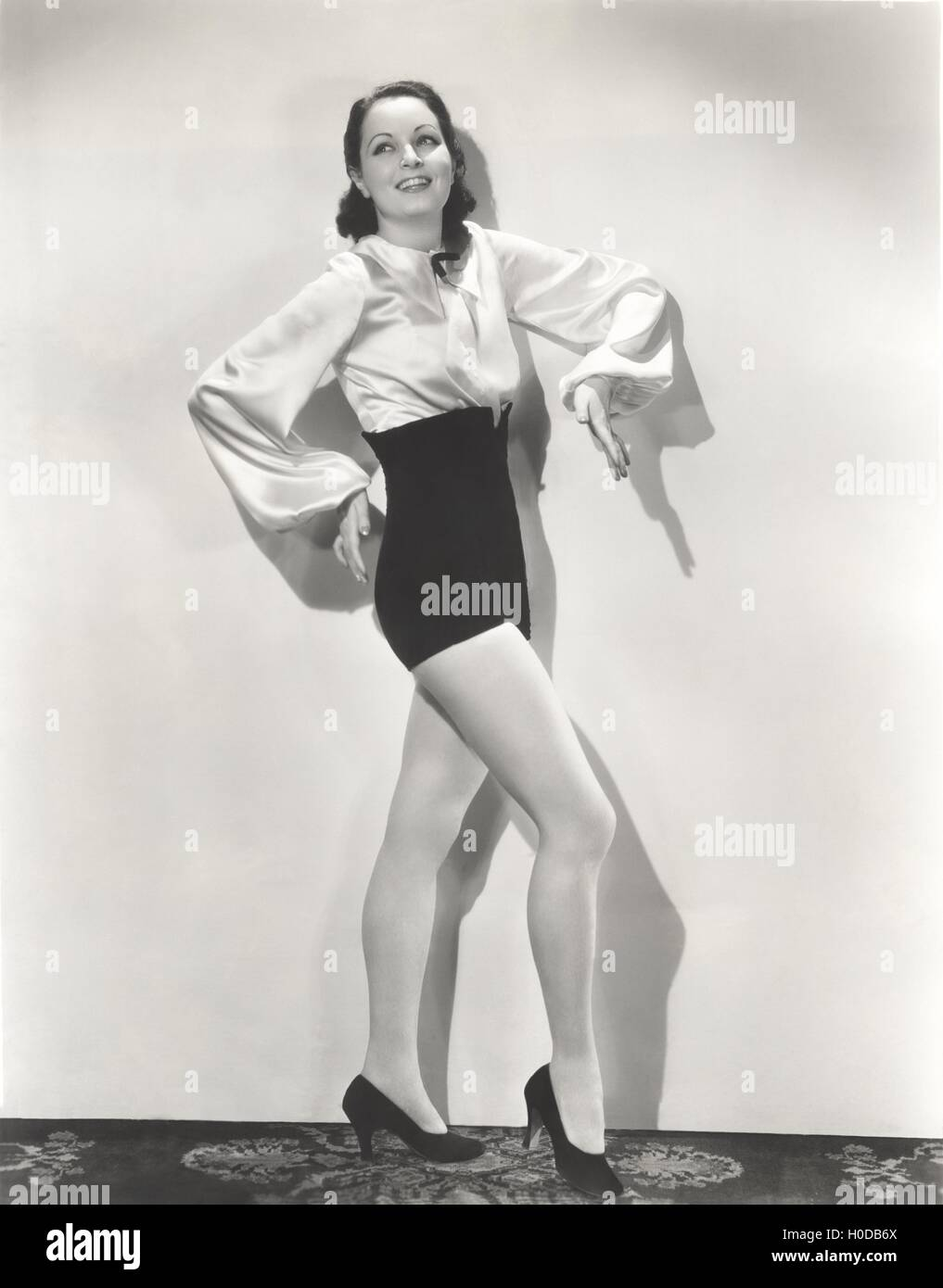 Dancer posing in high-waisted shorts and silk blouse - Stock Image