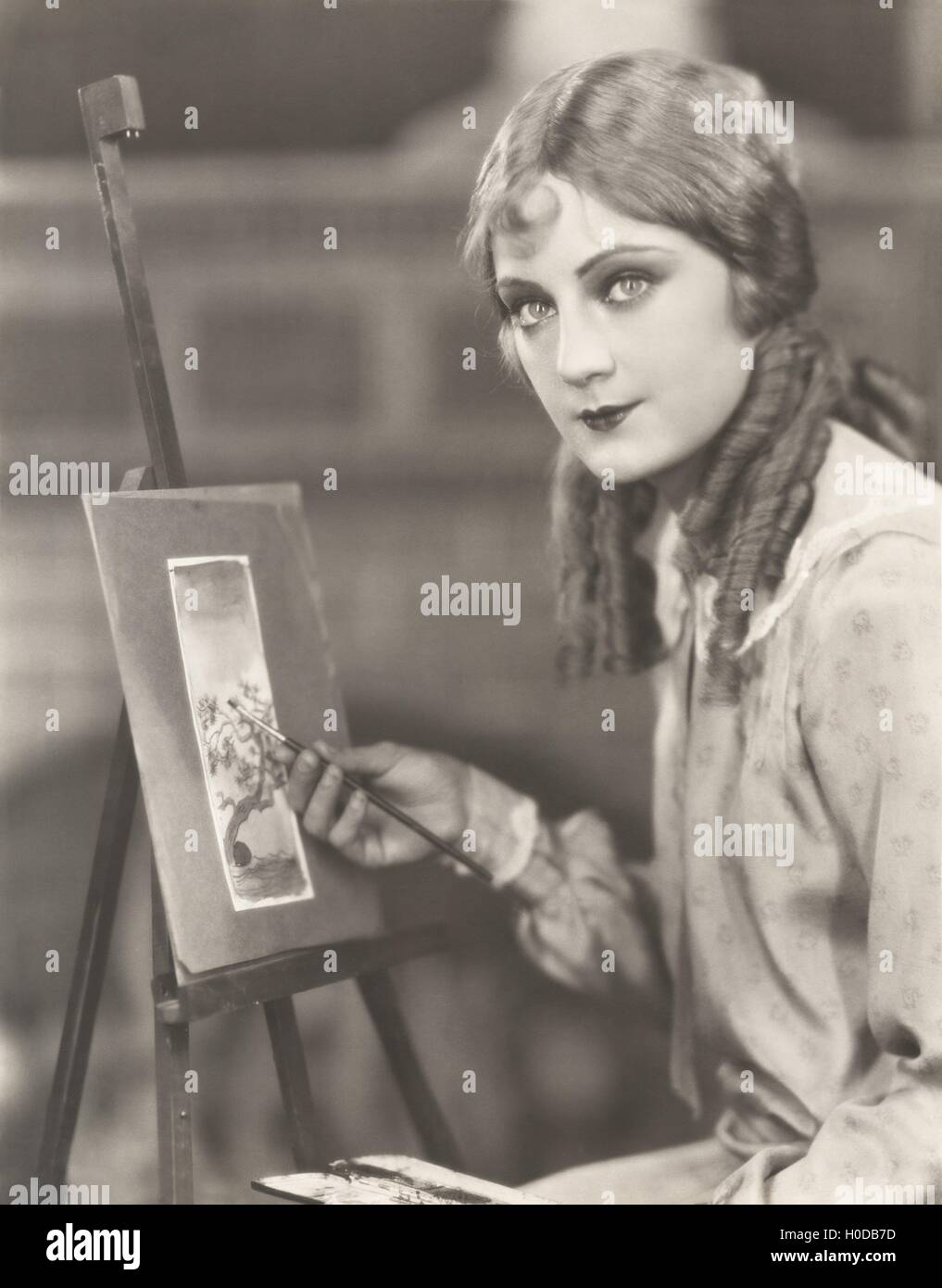Portrait of an artist with her easel painting a picture of a tree - Stock Image