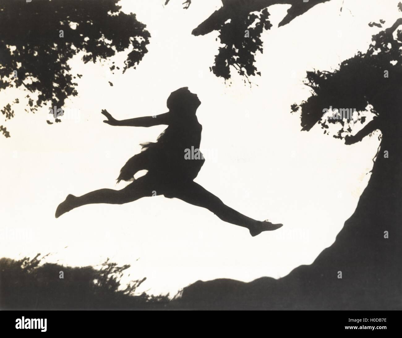 Silhouette of a woman in mid-air jumping between two trees - Stock Image