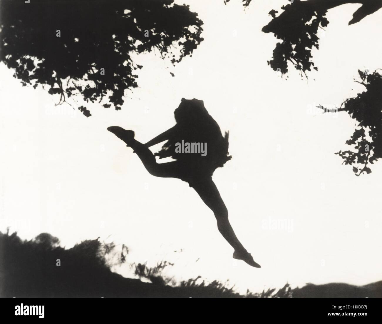 Silhouette of woman leaping in mid-air - Stock Image