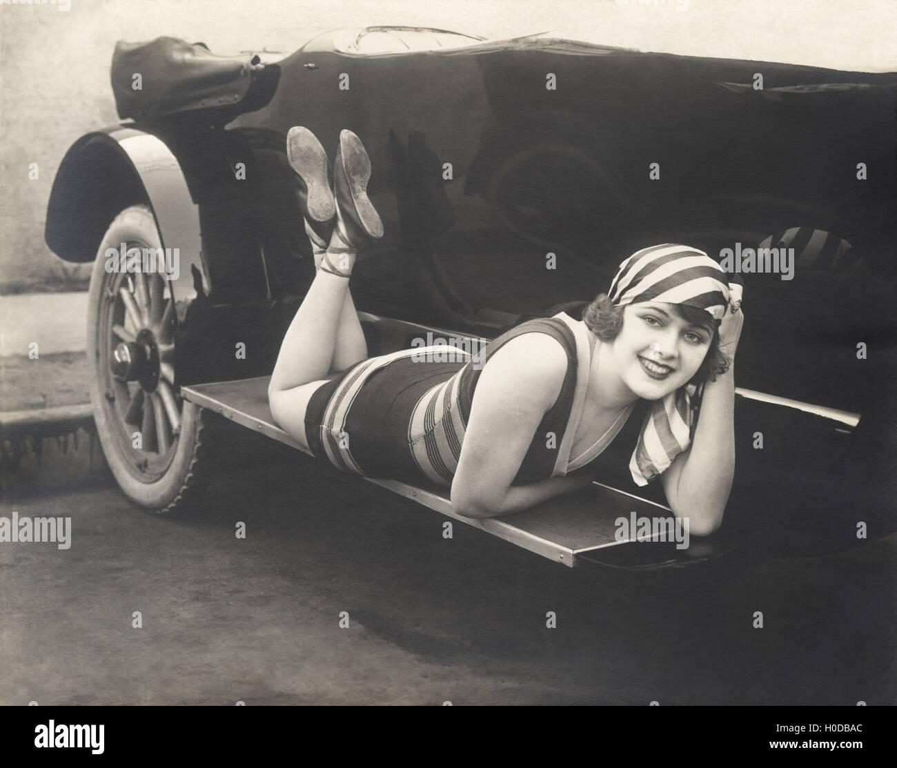 Bathing beauty posing on running board of convertible - Stock Image