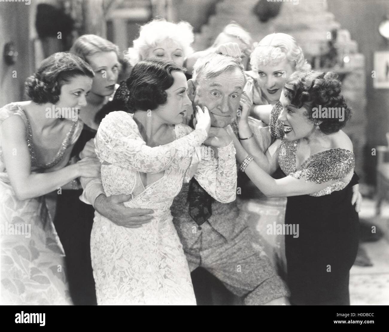 Elderly man surrounded by flirtatous young women - Stock Image