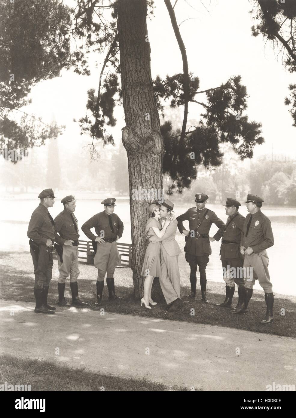 Police officers surrounding romantic couple in park - Stock Image