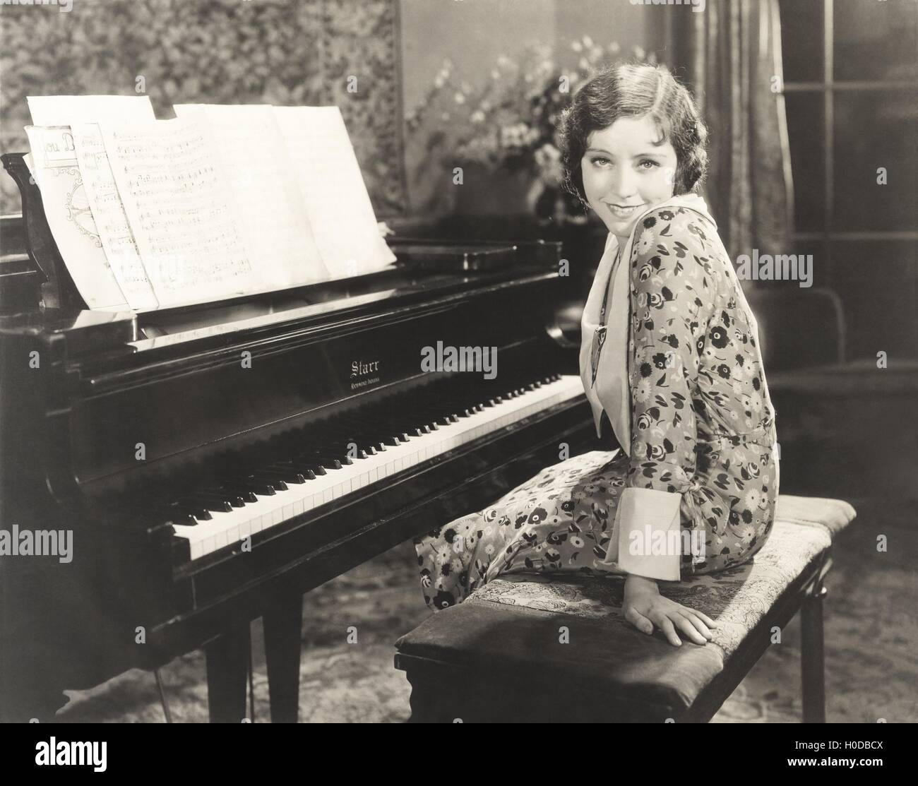Smiling woman sitting by piano at home - Stock Image