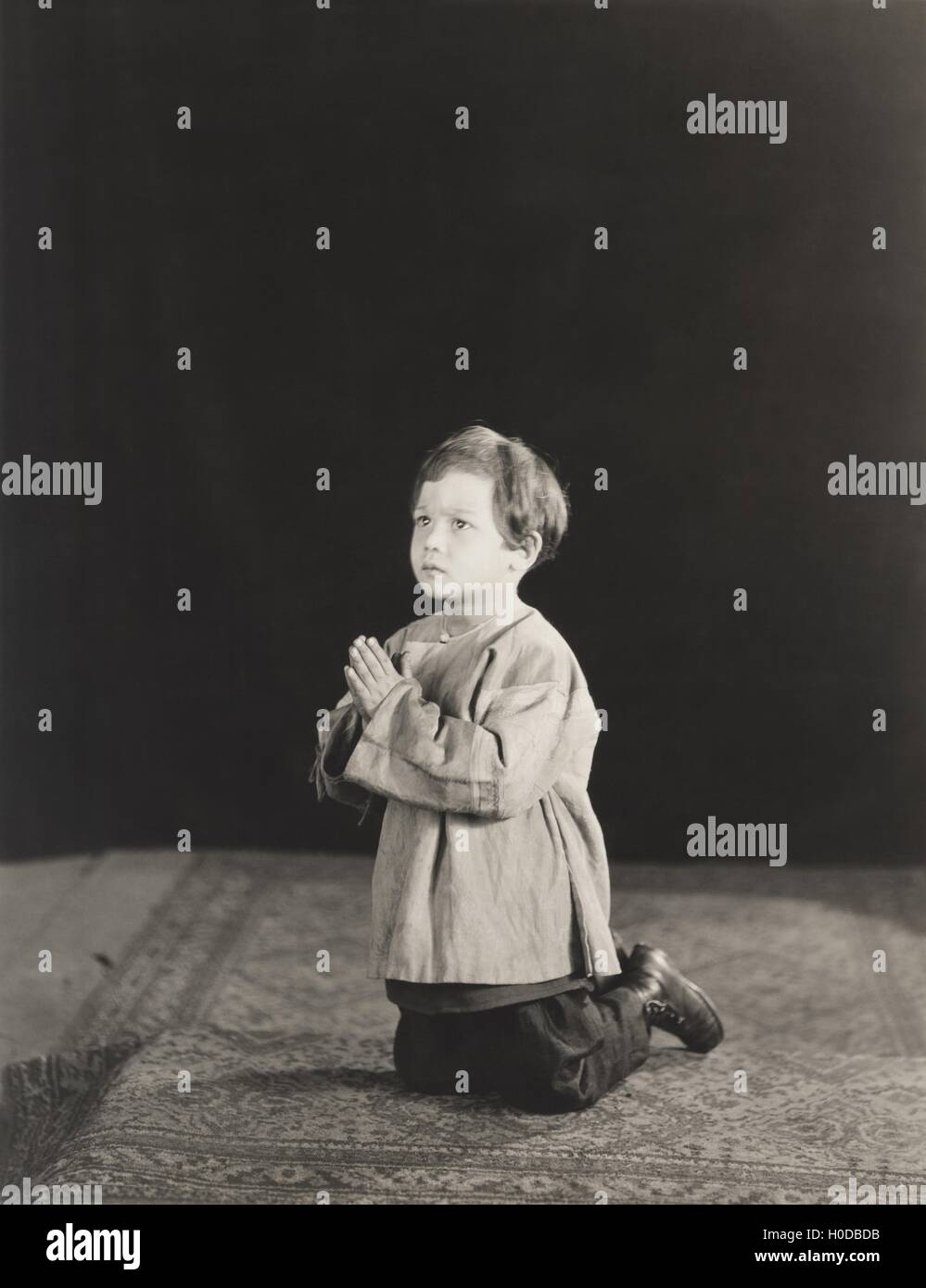 Little boy kneeling in prayer - Stock Image