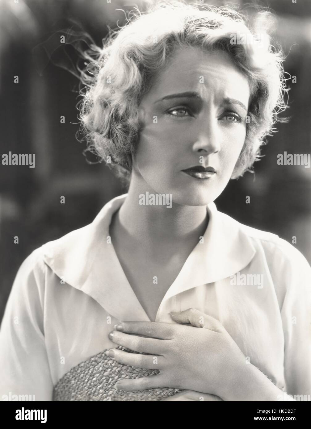 Sad woman clutching her heart - Stock Image