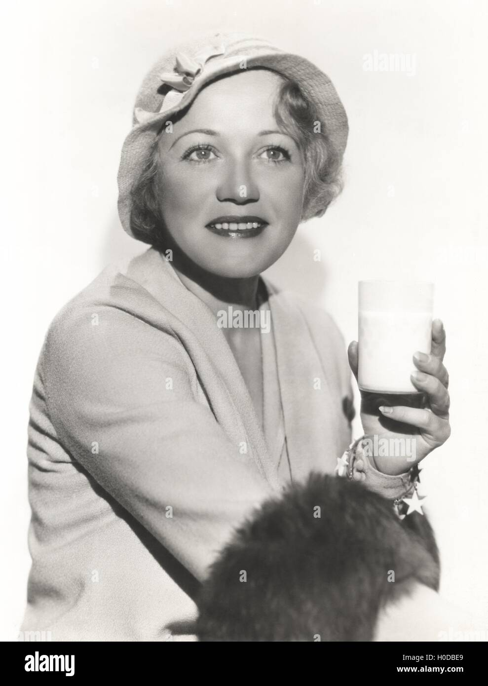 Woman in hat holding a glass of milk - Stock Image
