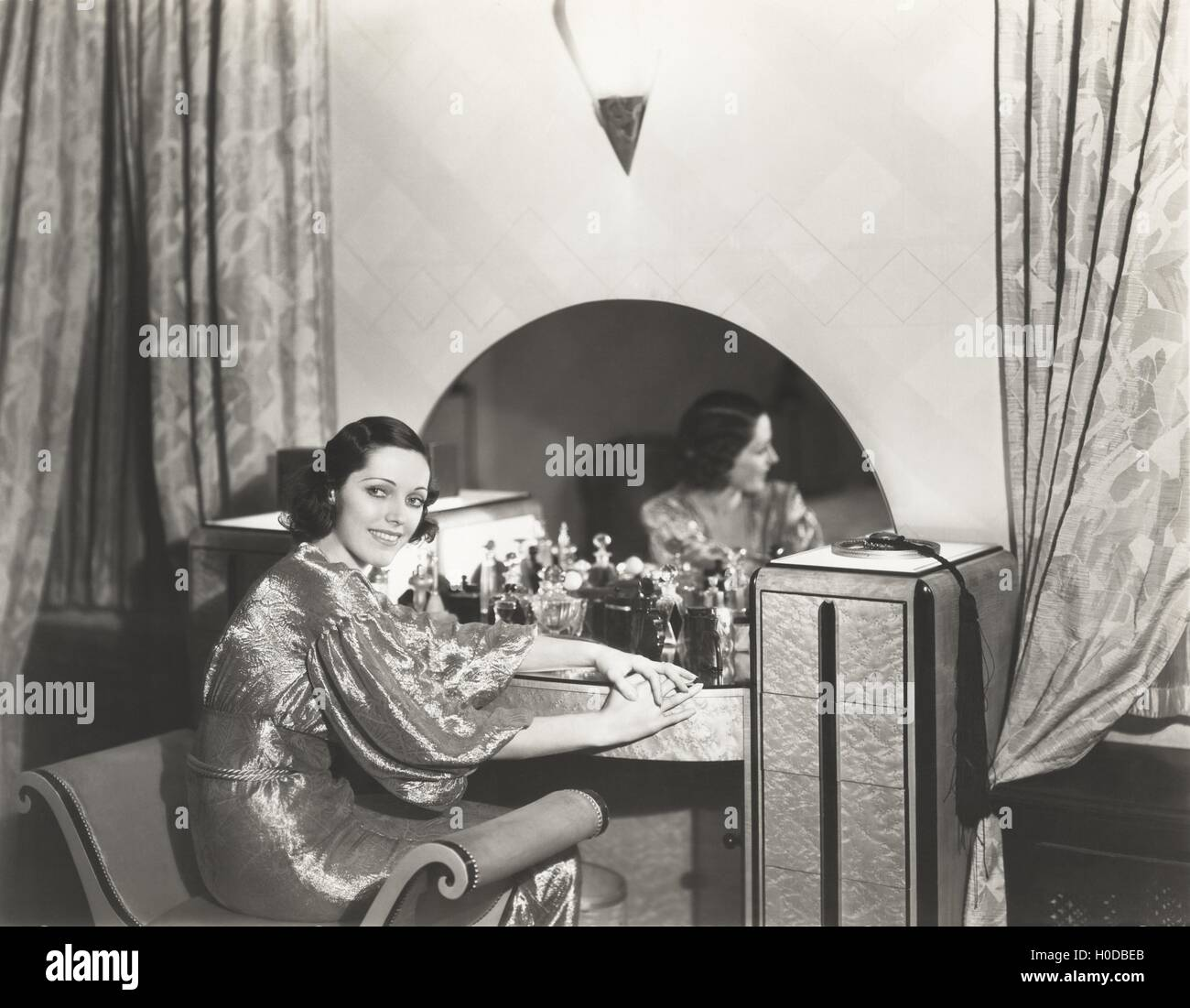 Woman in metallic dress sitting at her dressing table - Stock Image