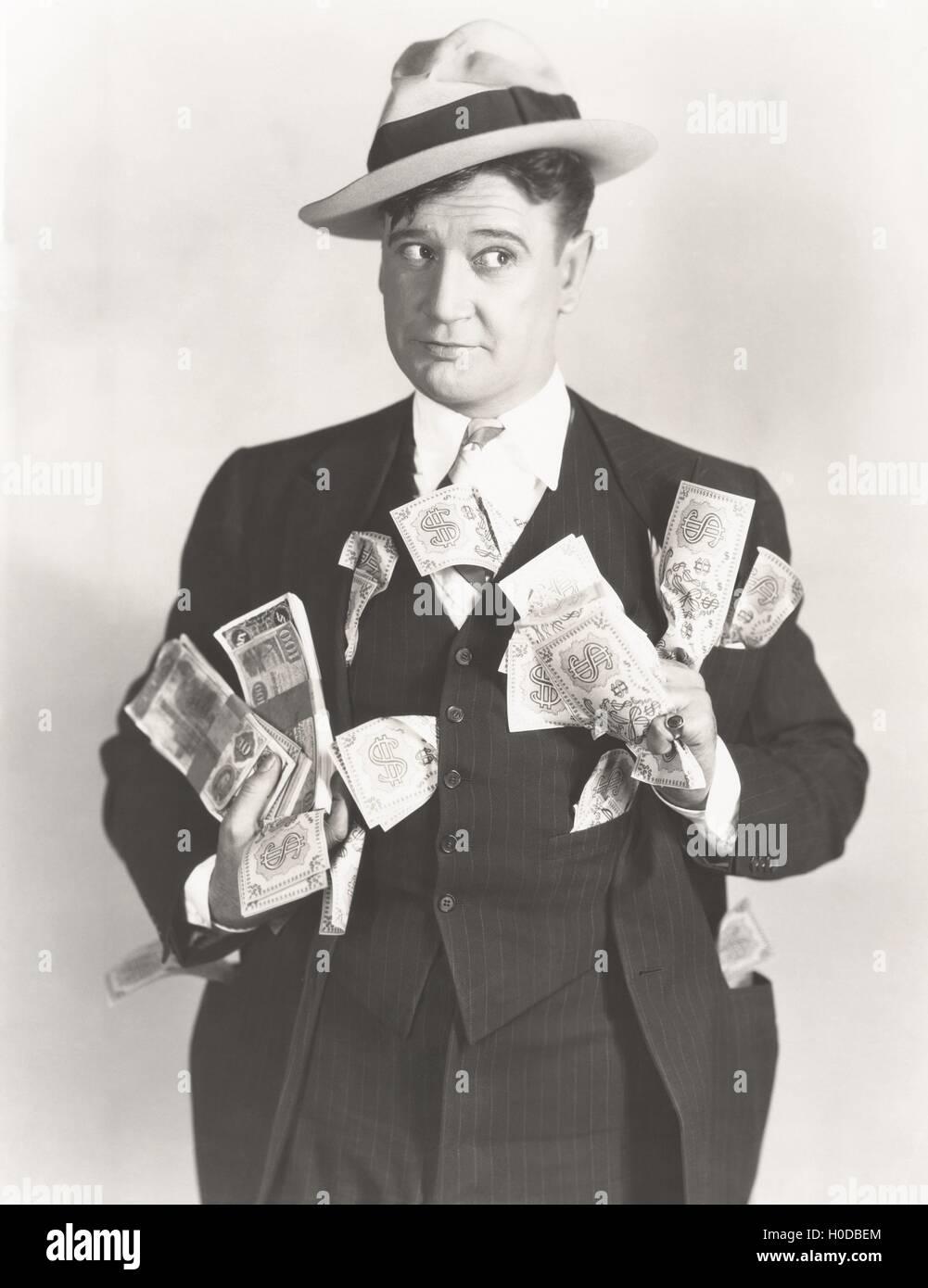Man holding wads of fake money - Stock Image