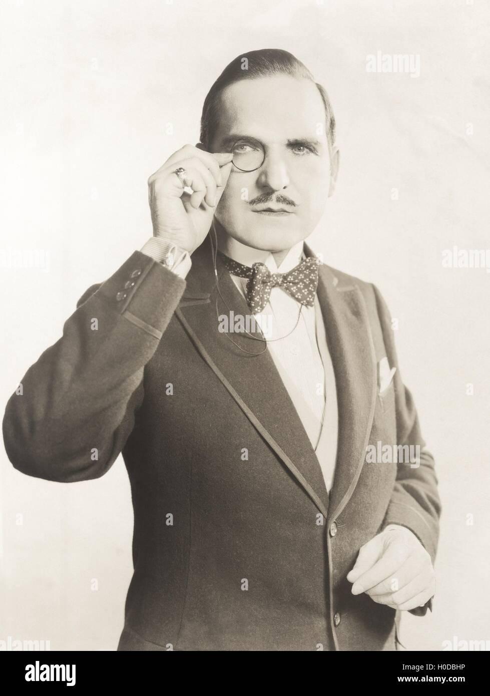 Man peering through monocle - Stock Image