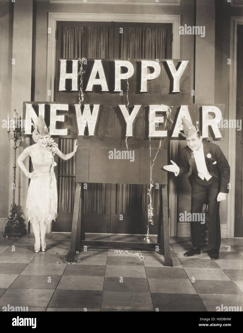 Couple ringing in the New Year - Stock Image
