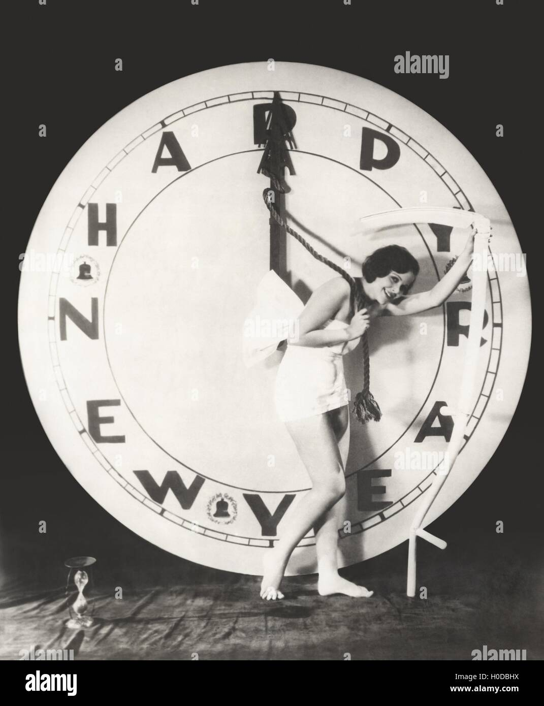Woman pulling the hour hand of giant clock on New Year's Eve - Stock Image