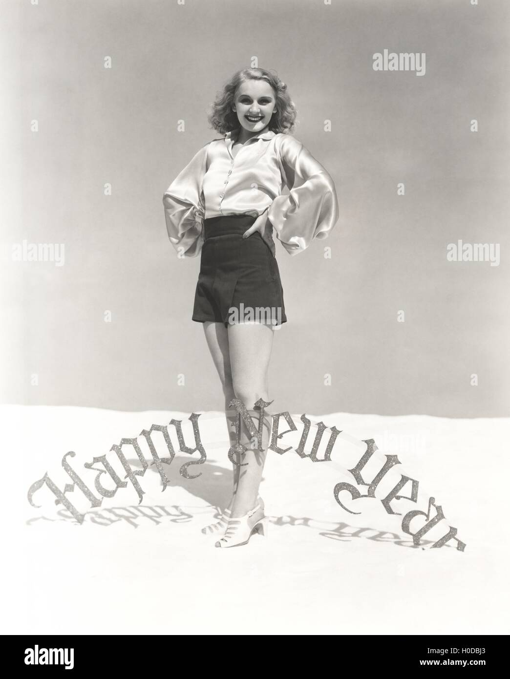 Portrait of smiling woman standing by Happy New Year sign - Stock Image